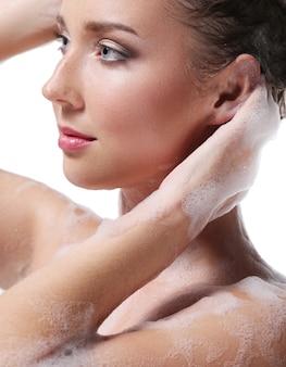 Femme se douchant avec du savon sur le corps et la tête. concept d'hygiène et de soin de la peau