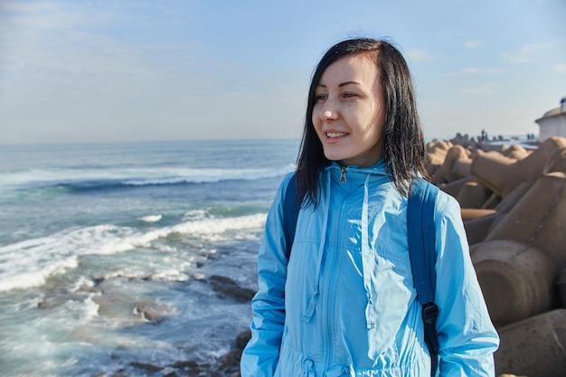 Femme se dresse sur la rive de l'océan atlantique, les vagues qui font rage frappant le rivage, le surf. casablanca, maroc
