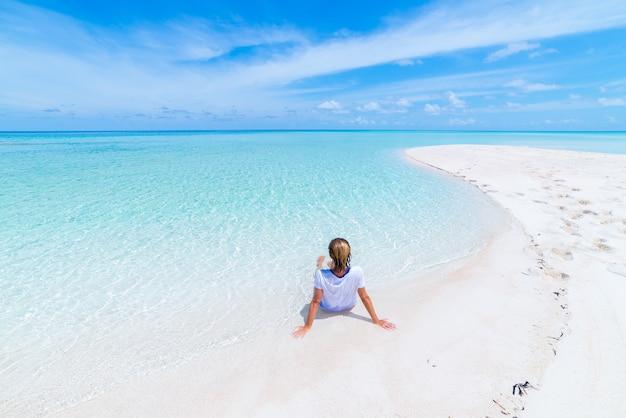 Femme se faire bronzer sur la magnifique plage de sable blanc, vue arrière, journée ensoleillée, eau transparente turquoise, vraies personnes. indonésie, îles wakatobi