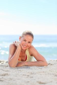 Une femme se faire bronzer à la plage