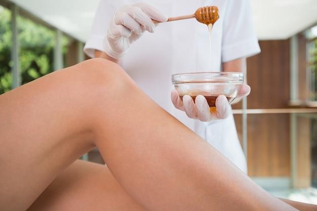 Femme se faire cirer les jambes par une esthéticienne