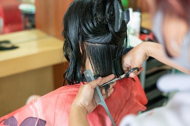 Femme se faire couper les cheveux par une main de coiffeur dans un salon