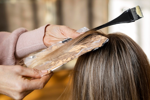 Femme se faire teindre les cheveux par un coiffeur à la maison