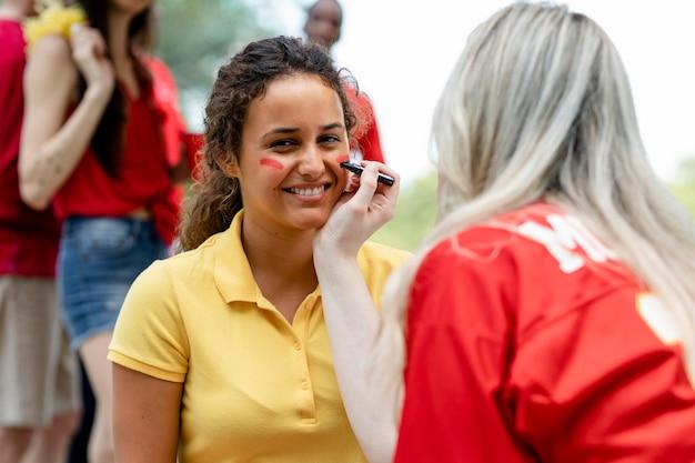 Une femme se fait peindre les joues aux couleurs de son équipe