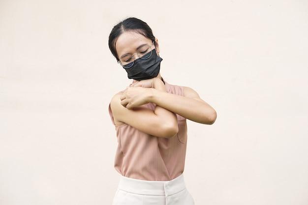 Femme se grattant le bras de démangeaisons sur fond gris clair