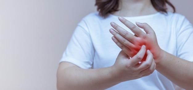 Femme se grattant la démangeaison sur les mains, réaction allergique aux piqûres d'insectes, dermatite, aliments, médicaments.