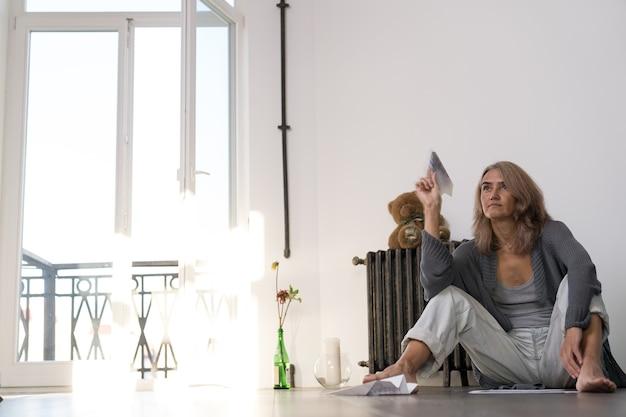 Une femme se lance dans un avion en papier dans son appartement