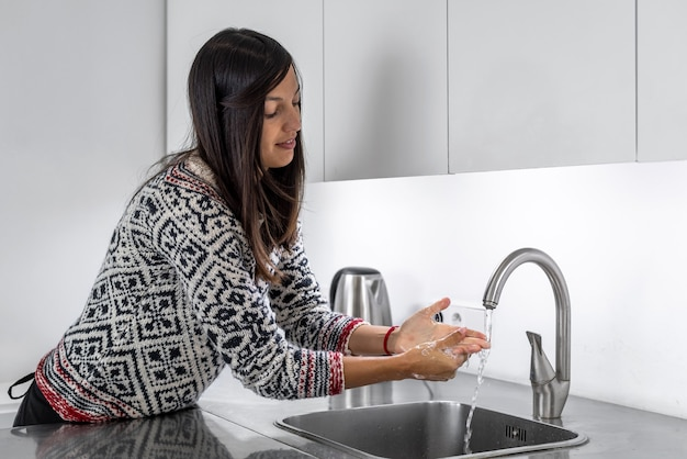 Femme se lavant les mains après la cuisson