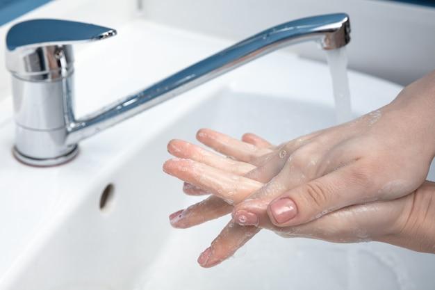 Femme se lavant soigneusement les mains avec du savon et du désinfectant, gros plan.
