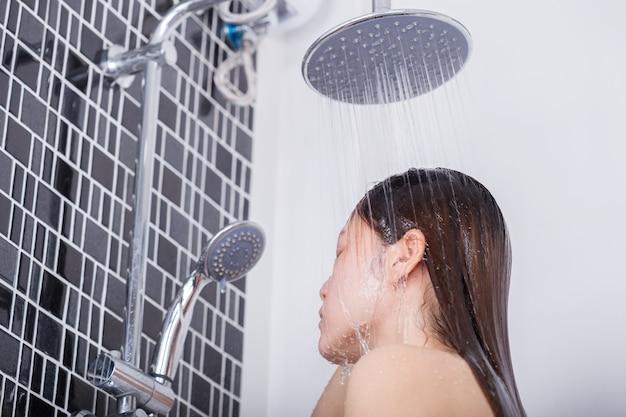 Femme se lave les cheveux et le visage par la pluie