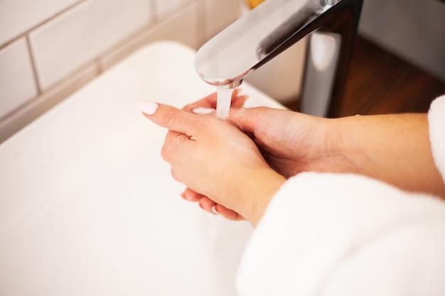 Femme se lave les mains dans une salle de bain lumineuse