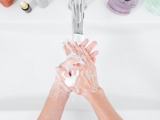 Une femme se lave les mains avec du savon sous un robinet d'eau dans la salle de bain. produits d'hygiène et de désinfection. concept d'hygiène en détail. vue de dessus, soins de santé.
