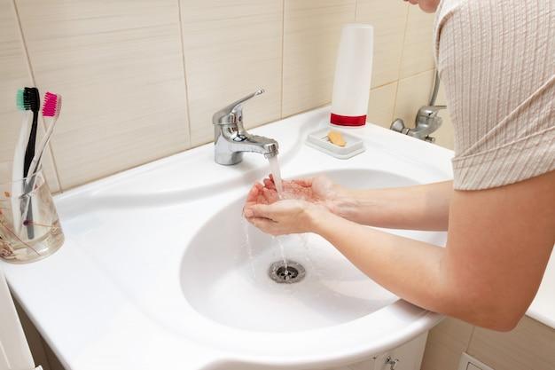 Une femme se lave les mains avec de l'eau dans un lavabo