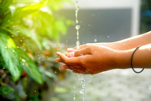 Femme se lave les mains avec de l'eau