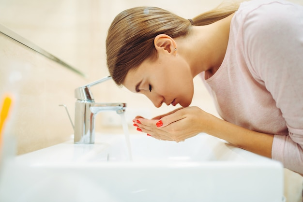 Femme se lave le visage au lavabo de la salle de bain