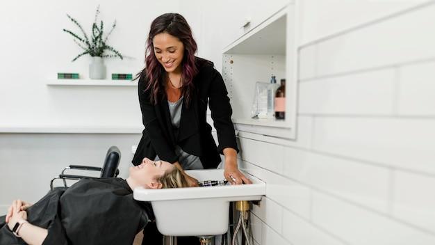 Femme se laver les cheveux dans un salon de beauté