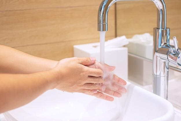 Femme se laver les mains avec du savon liquide