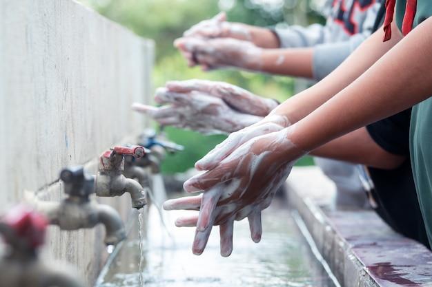 Femme se laver les mains avec un savon liquide