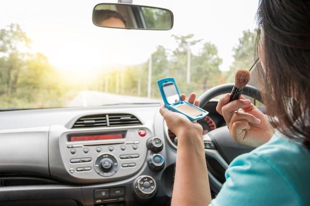 Femme se maquiller en conduisant une voiture