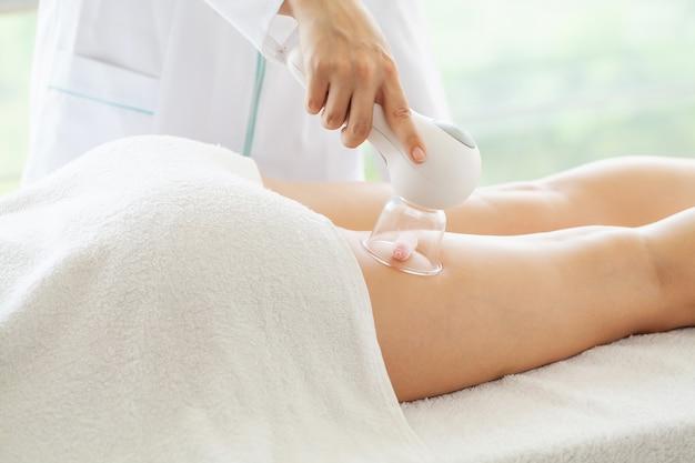 Femme se massage au gpl pour les soins de la peau en studio de beauté