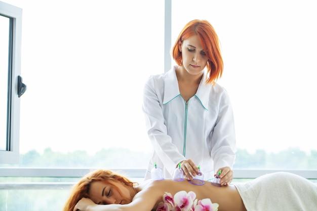 Femme se massage avec l'utilisation de bidons sous vide.