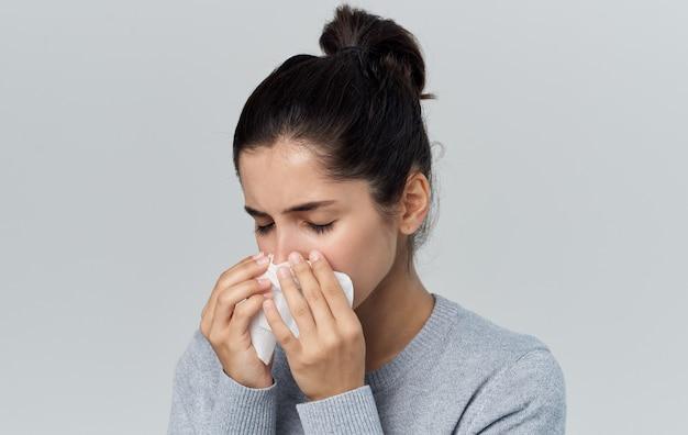 Femme se mouche dans une serviette nez qui coule problèmes de santé fond gris. photo de haute qualité