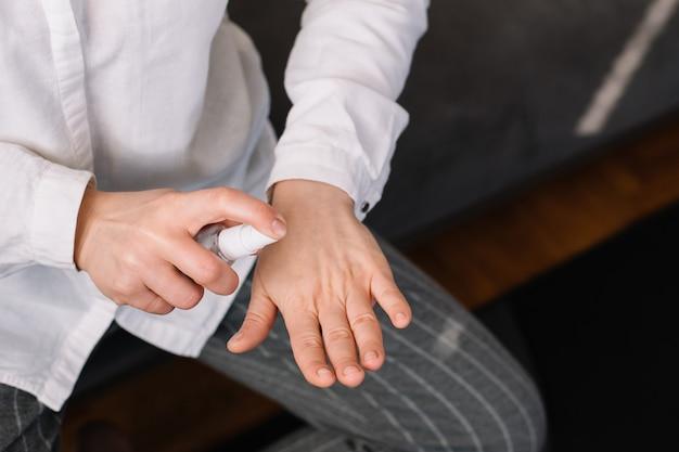Femme se nettoie les mains avec un spray pour le lavage des mains à base d'alcool