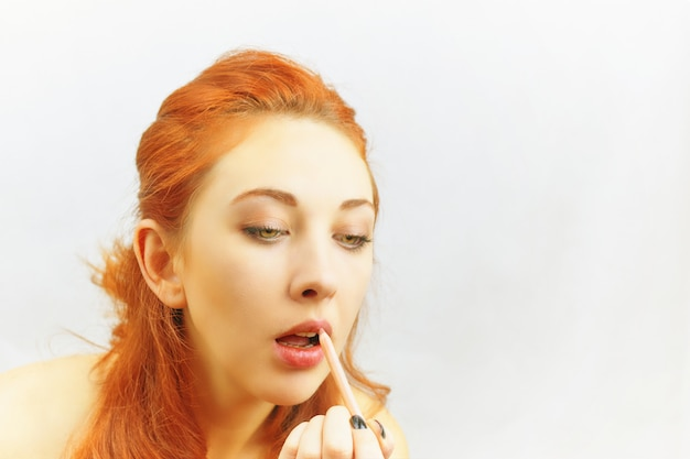 La femme se peint les lèvres.