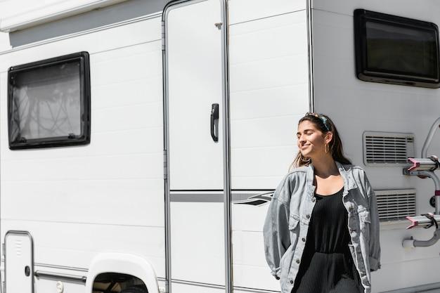 Femme se penchant sur le camping-car avec les yeux fermés