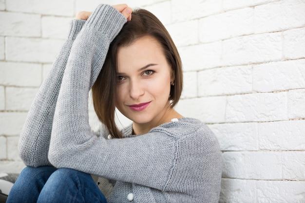 Femme se penchant sur le mur regardant la camara