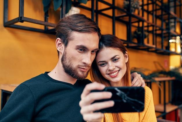Une femme se photographie et un jeune homme à une table dans un café-restaurant couple d'amis amoureux