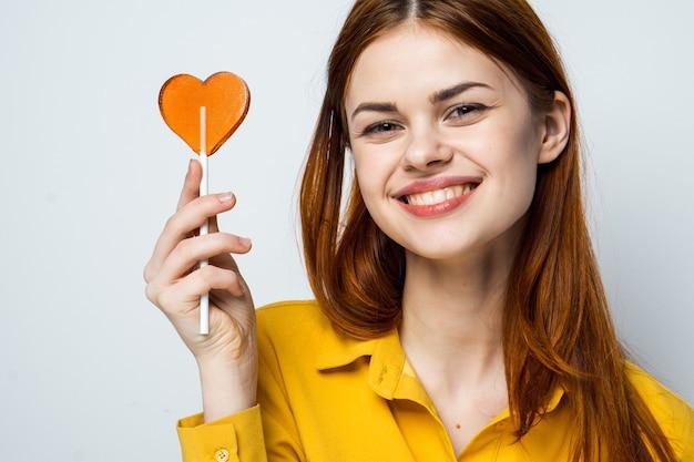 Femme se plaignant avec sucette en mains émotions chemise jaune vue recadrée.