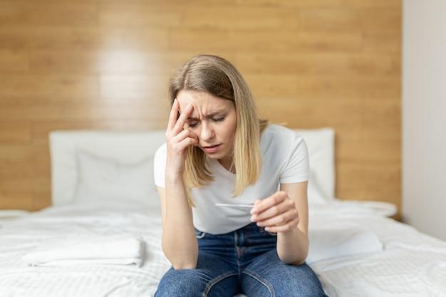 Une femme se plaint d'un test de grossesse assis sur un canapé