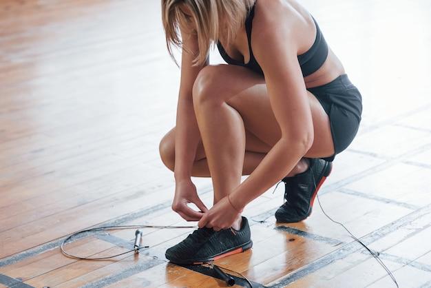 Femme se préparant à la formation. assis sur le sol d'une salle de sport moderne.
