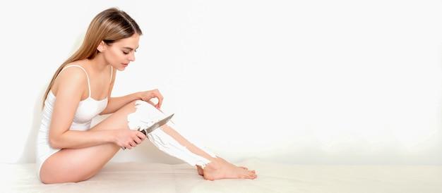 La femme se rase les jambes avec un couteau