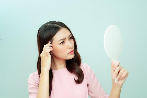 Femme se regardant dans un miroir à main