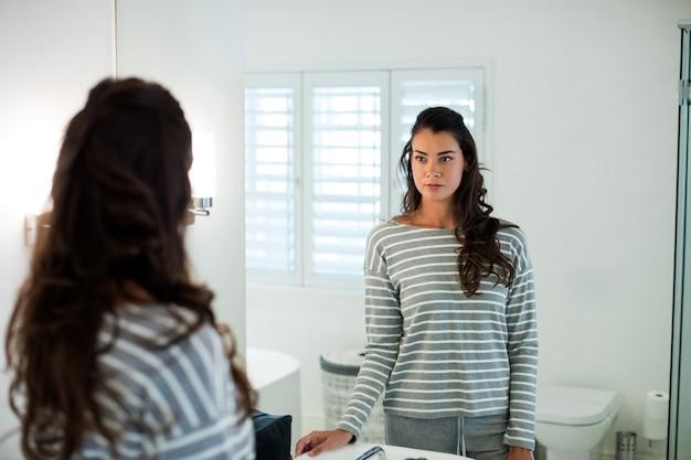 Femme se regardant dans le miroir de la salle de bain à la maison