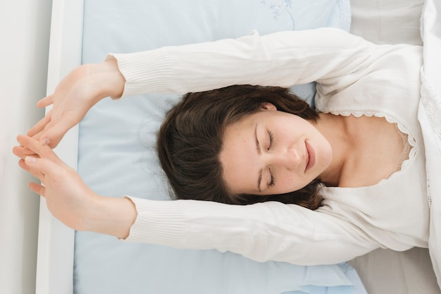 Femme se relaxant dans son lit