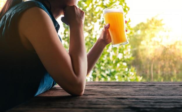 Femme se relaxant devant un verre de bière sur le balcon en été