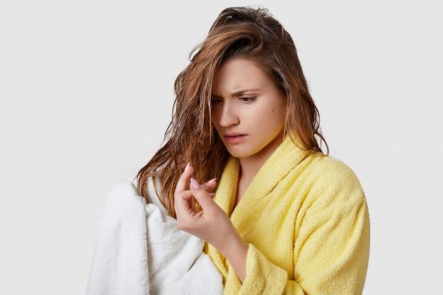 La femme se rend compte qu'elle a les cheveux abîmés, regarde les extrémités avec stress, qu'elle est mouillée après la douche, essuie avec une serviette blanche