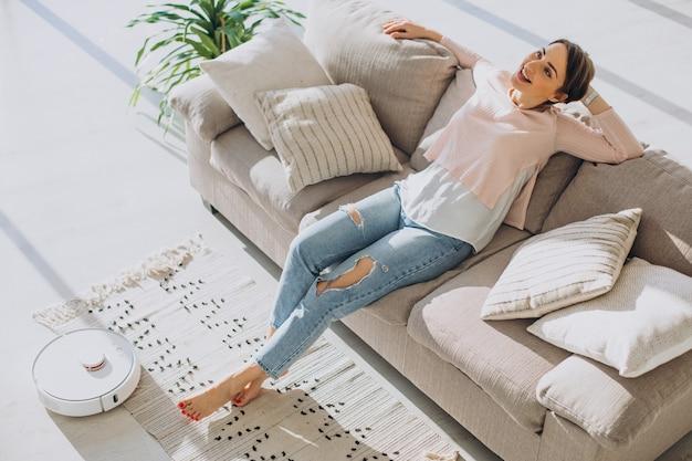 Femme se reposant sur un canapé pendant qu'un aspirateur robot fait le ménage