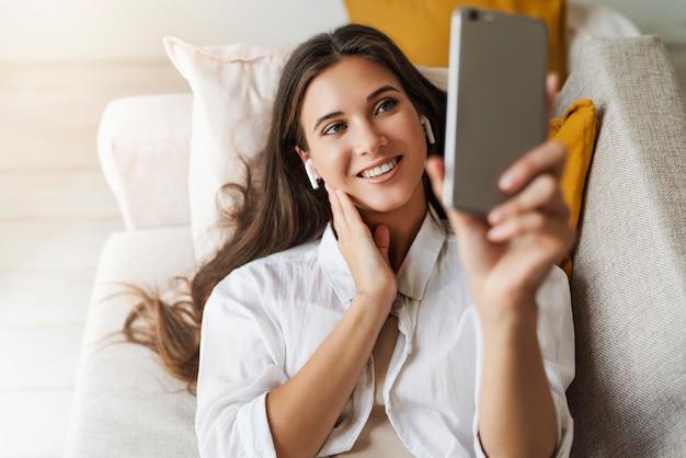 Femme se repose à la maison, utilise un smartphone pour communiquer avec des amis, vérifie ses e-mails.