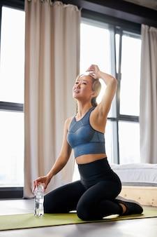 Femme se reposer après un entraînement intensif à la maison, tenant une bouteille d'eau dans les mains, assis sur un tapis dans une pièce lumineuse