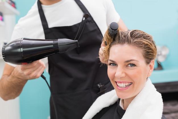 Femme se sèche les cheveux