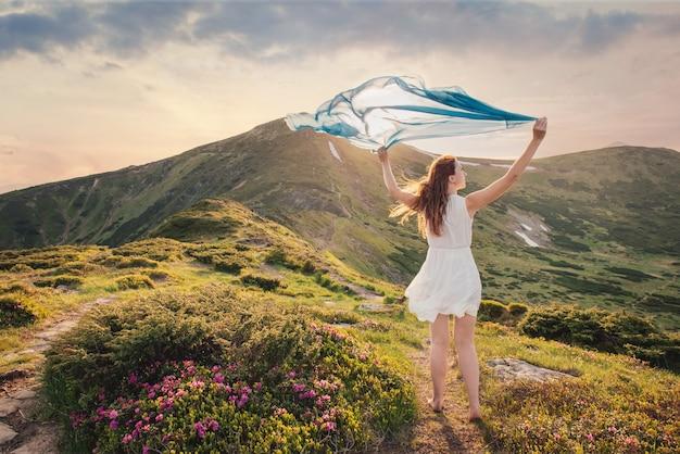 La femme se sent libre et profite de la nature dans les montagnes avec des tissus bleus dans les mains au coucher du soleil
