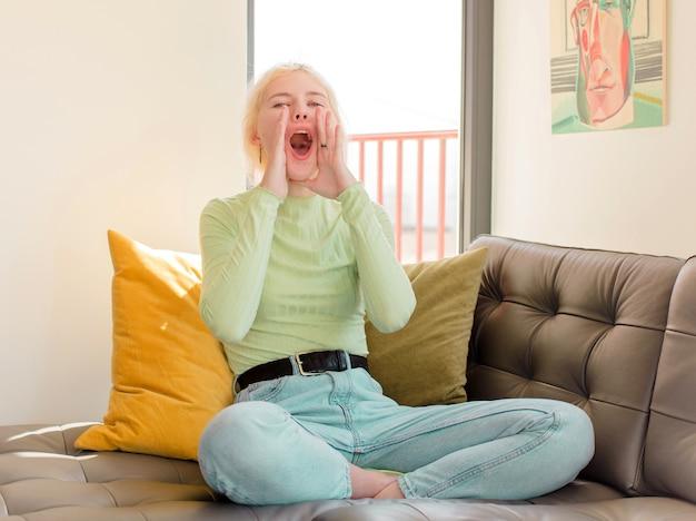 Femme se sentant heureuse, excitée et positive, donnant un grand cri avec les mains à côté de la bouche, appelant