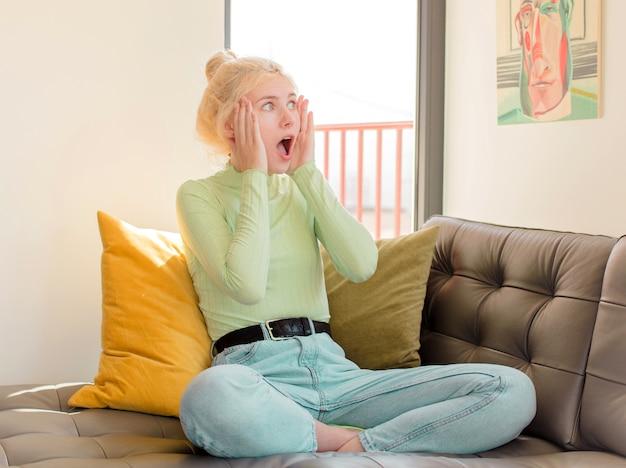Femme se sentant heureuse, excitée et surprise, regardant sur le côté avec les deux mains sur le visage