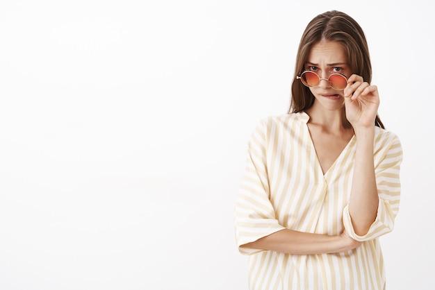 Femme se sentant incertaine à propos de l'offre suspecte, décoller les lunettes de soleil regardant sous le front et mordre la lèvre inférieure à cause de sentiments inquiets d'insécurité ayant des doutes et des hésitations
