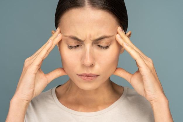 Femme se sentant mal de tête, faiblesse, massage des tempes, fatiguée, épuisée par le surmenage, isolée