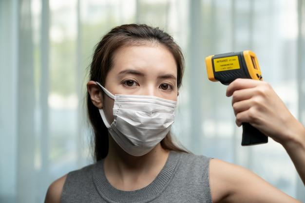 Femme se sentant malade portant un masque de protection. avec un contrôle de sécurité aux portes, utilisez un thermomètre numérique pour vérifier la température.